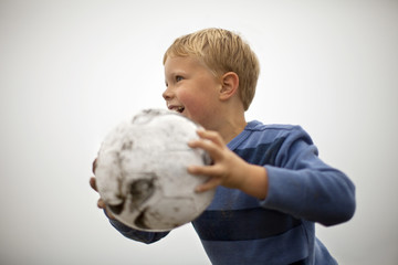 Young boy holding a soccer ball.