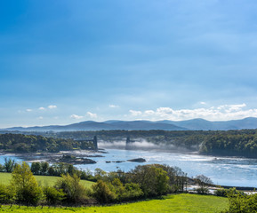 Menai Bridge and mist over the Menai straits between north Wales and Anglesey UK