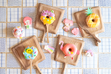 Cute donuts. 4 Cute sugar glazed doughnut with happy smiling face, a cute monster doughnut, pineapple and flamingo doughnuts, top view. Creative idea for fun birthday or private fancy party.