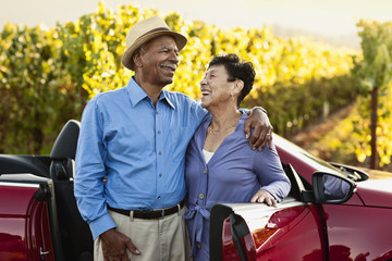 Happy senior couple standing next to their convertible by the vineyard.