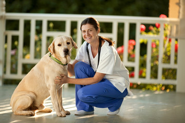 Young female nurse playing with a dog on the verandah of someone's home.