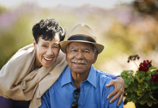 Portrait of happy senior man sitting by his wife.