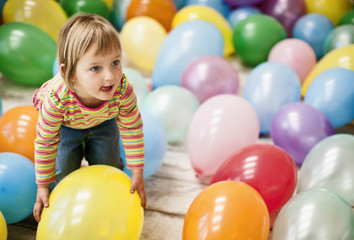 Little girl having fun in a room full of balloons.