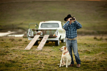 Farmer looking through binoculars on a paddock with his dog by his side.