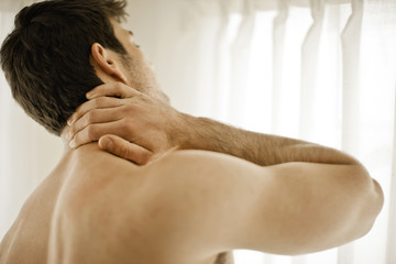 Shirtless young man rubbing his neck in pain.
