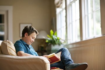 Teenage boy sitting in a living room reading a book.