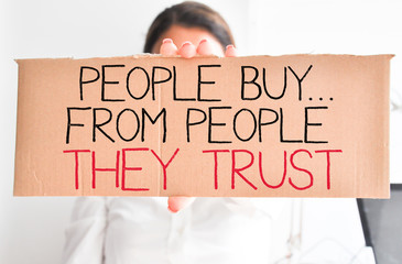 "Business woman holding white card with text ""people buy from people they trust"""