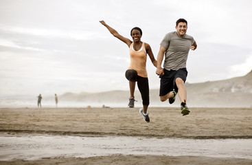Smiling young couple jumping over shallow water on a beach.