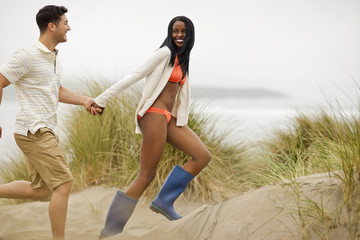 Smiling young couple holding hands while running through sand dunes.