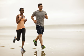 Young couple running together on a beach at low tide.