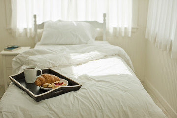 Breakfast tray of tea and pastries on top of a bed.