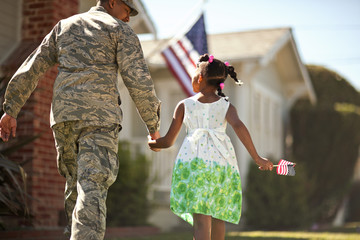 Young girl holding hands with her father as they walk towards their home.