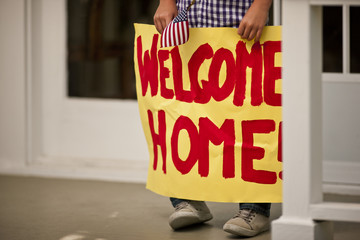 Welcoming sign held by a boy as he stands on the front porch of his home.