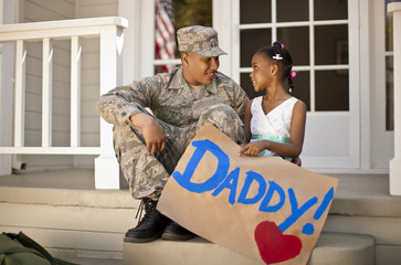 Young girl and her father having a discussion on the front porch of their home.