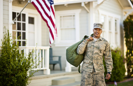 Portrait of young soldier standing outside his home