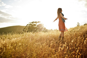 Young woman standing with her arms outstretched in a grassy field.