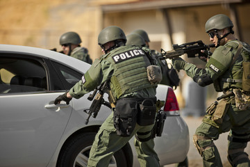 Group of police officers surround a vehicle during an exercise at a training facility.