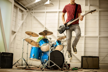 Two teenage boys playing musical instruments in a garage.