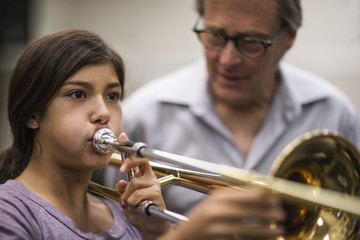 Teenage girl learning to play trombone.