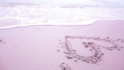 Beautiful heart picture on sand beach background.