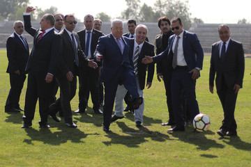 Palestinian President Mahmoud Abbas kicks a ball at Club Deportivo Palestino soccer club as they meet in Santiago