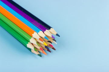 A bunch of colored pencils lying on a blue background.