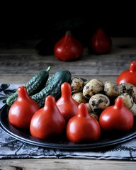 On a wooden table on a metal dish fresh vegetables - tomatoes, potatoes and cucumbers