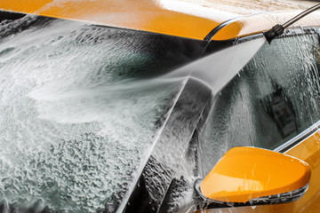 Detail on dark yellow car windshield ad side mirror being washed with water jet spray, cleaning soap foam.