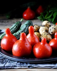 On a wooden table on a metal dish fresh vegetables - tomatoes, potatoes and cucumbers. Tomatoes droplets of water