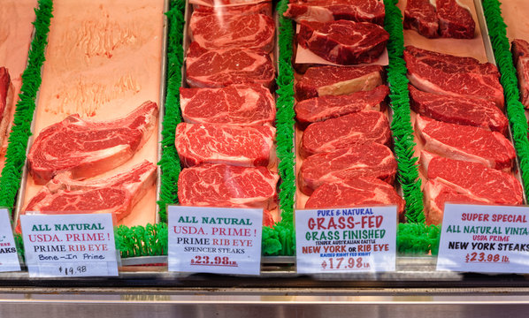 A group of assorted beef steaks at a market