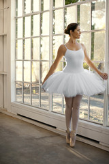 Mid adult woman looking out a window while wearing a ballet costume.