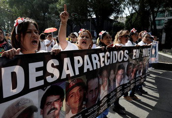Mothers and relatives hold pictures of missing people as they march in Mexico City