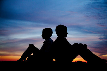 Silhouette of  2 Boys Sitting Back to Back with Sunset Behind THem