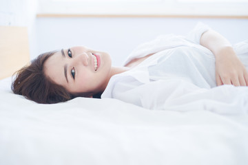 beautiful Asian woman smiling on bed