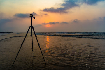 tripod in background of sunrise at sea beach for beach photography with space for text