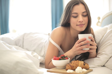 Beautiful girl having breakfast in the bed