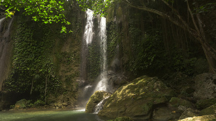 Beautiful waterfall in green forest in jungle. Waterfall with natural swimming pool in a mountain river canyon. Philippines, Bohol.
