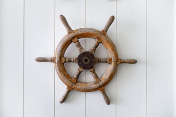 Old boat steering wheel mounted on the white wall