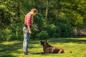 Young woman tell dog to lay down on grass,obedience training