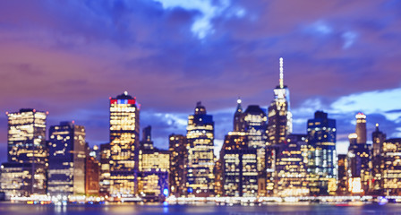 Blurred color toned Manhattan waterfront skyline at night, urban background, New York City, USA.