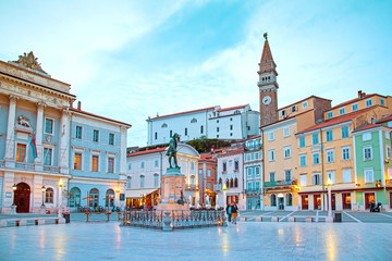 Beautiful street landscape on the central square with a monument and an ancient watch tower in Porec, Croatia's tourist center.