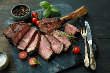 Sliced barbecued tomahawk rib tip with rosemary, salt and herbs on dark background