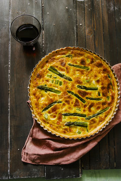 Quiche with green asparagus, cream, scamorza cheese and spec ham, round shaped on an aluminium mold, top view over a wooden board with ingredients around and a glass of red wine.