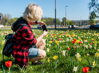 Young woman taking pictures of flowers. Spring concept