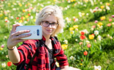 Young pretty blonde woman in black glasses takes selfie floral meadow on background. Spring concept