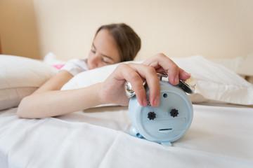 Closeup image of sleeping young girl holding hand on alarm clock