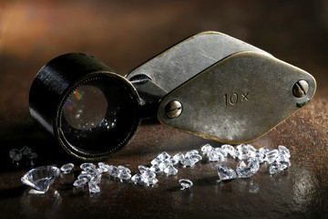brilliant cut diamonds with folding magnifier on wooden background