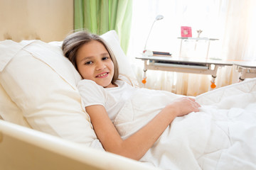 Portrait of beautiful teenage girl lying in bed and looking in camera
