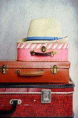 Travel suitcase isolated. Vintage suitcase with hat on the light background