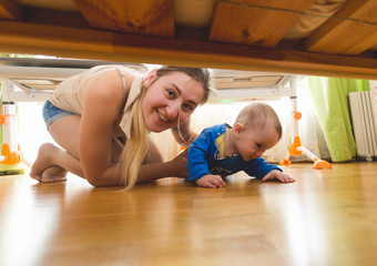 Beautiful young mother with toddler boy lying on floor and looking under the bed